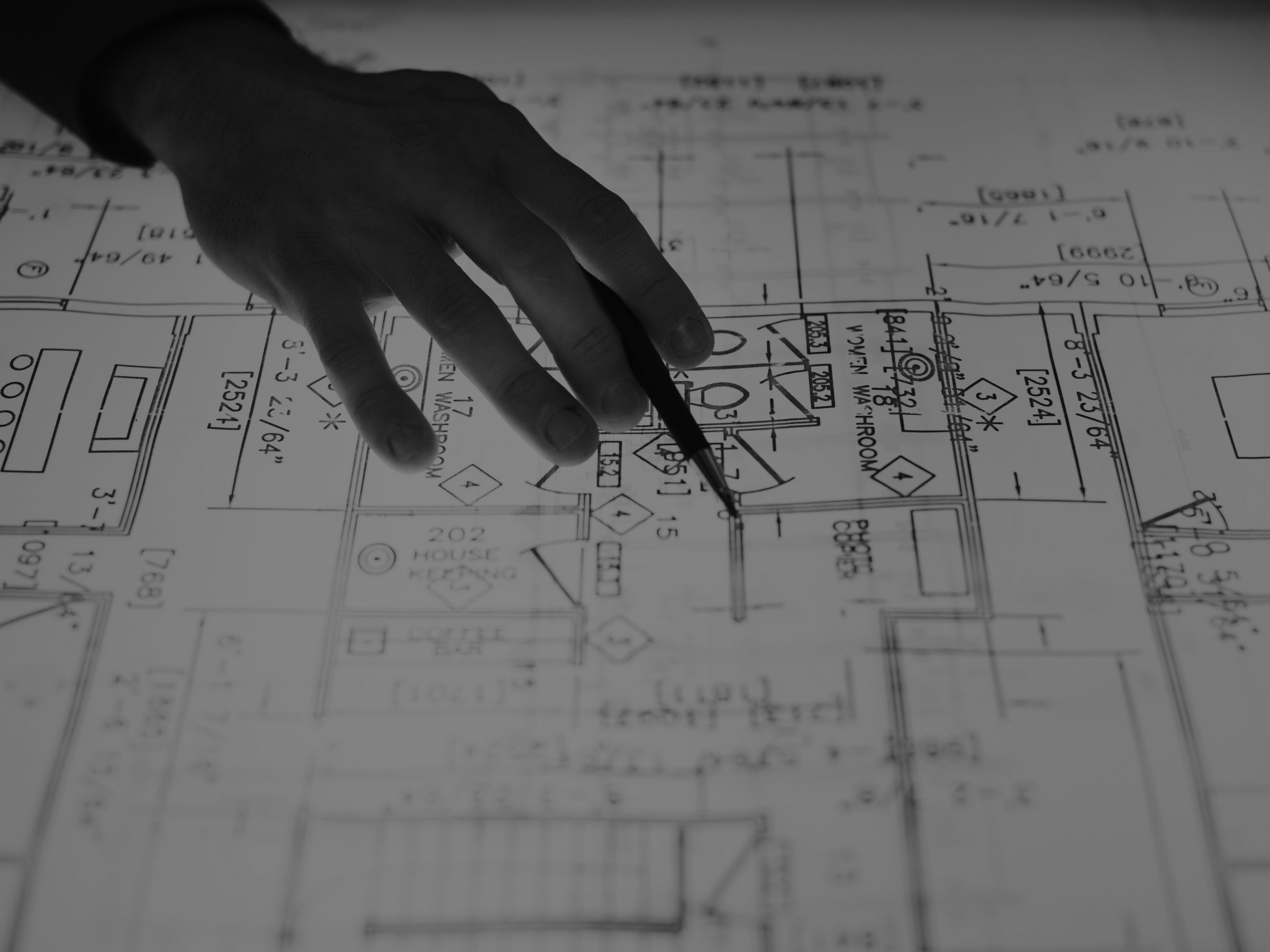 Hand pointing at blueprints with a pencil