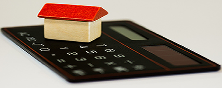 Image of a toy wooden house on a black calculator